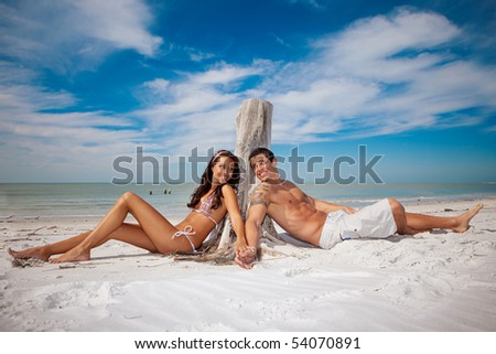 Couple sitting at a beach, happy