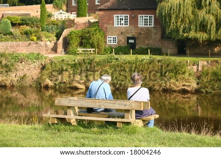 couple sitting on bench overlooking river
