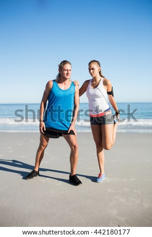 Couple stretching at the beach on a sunny day