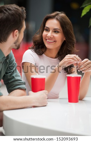 Couple talking. Cheerful young couple talking and drinking soda