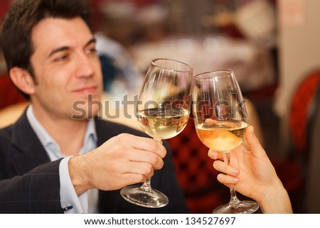 Couple toasting wineglasses in a restaurant