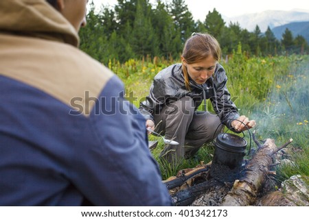 Couple tourists sitting near by the campfire and cooking dinner