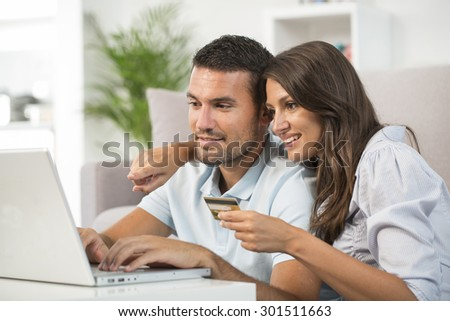 Couple using credit card to shop on line
