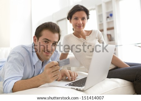 Couple using credit card to shop on line. Laptop.indoor on sofa