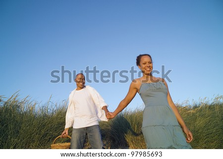 Couple walking and holding hands at beach