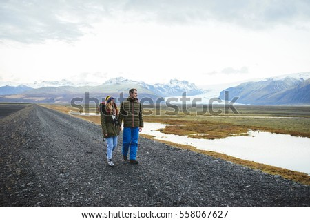 couple walking with camera and looking at mountains