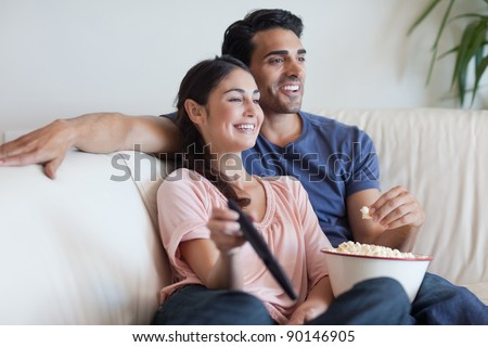 Couple watching TV while eating popcorn in their living room