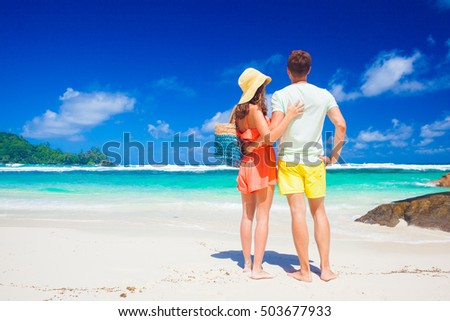 Couple wearing bright clothes on a tropical beach on Mahe island, Seychelles