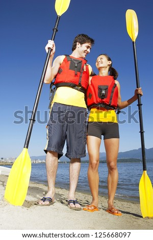couple wearing red life jackets, standing on the beach side by side holding kayak paddle, looking at each other, blue sky and mountains seen at the back