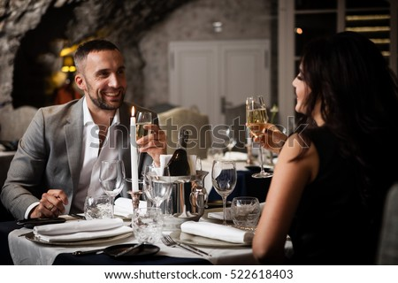 Couple with champagne glasses dating and toasting in restaurant