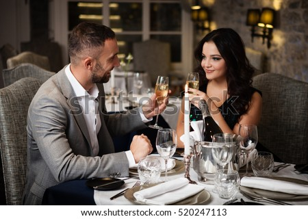 Couple with champange glasses dating and toasting in restaurant