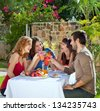 Couples enjoying a healthy outdoor lunch. Couples enjoying a healthy outdoor lunch in the garden laughing and joking as they toast each other with their drinks - stock photo