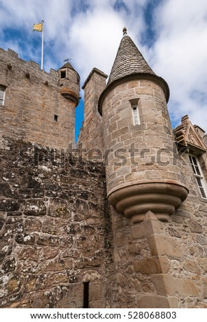 Cowdor, Scotland - June 2, 2012: Closeup of the brown-gray stone structure of gate and watchtower of undamaged Cowdor Castle. Flag on top.