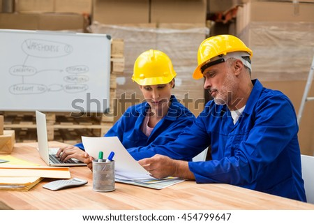 Coworkers looking at document in warehouse
