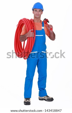 craftsman holding a hose pipe and spanner