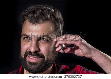 Crazy bearded young scratching his head with scissors