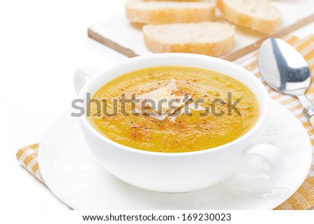 Cream soup of yellow lentils with vegetables in a bowl, isolated