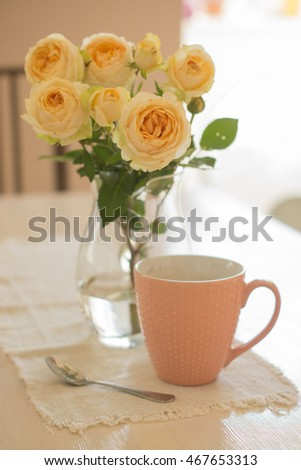 Creamy beautiful roses on a table with a cup on a linen napkin