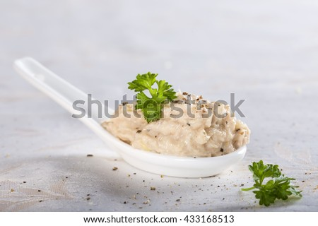 Creamy fish pate in spoon made with tuna, onion and butter