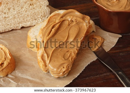 Creamy swirls of peanut butter on freshly baked italian bread with knife and crumpled parchment paper over rustic wood cutting board.  Closeup with soft natural lighting and shallow dof.