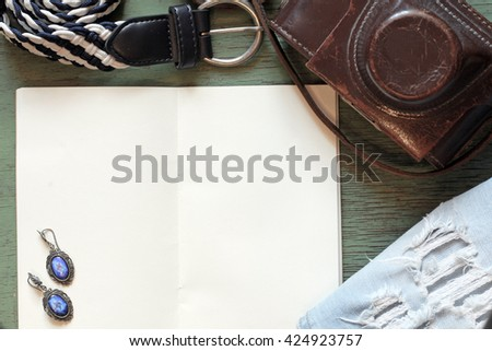 Creative arrangement of natural things with vintage camera and women's casual travel accessories, sketchbook note pad with empty paper page, wooden background, overhead view. Flat lay