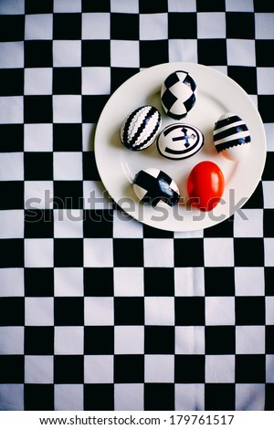 Creative Easter eggs on plate against chess background
