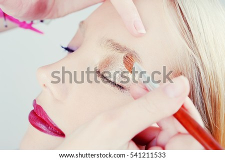creative make up applying by artist in studio