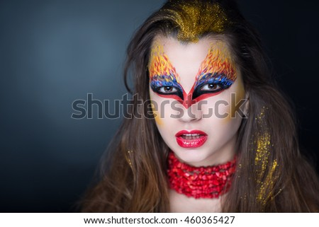 Creative makeup, crazy conceptual idea for Halloween. red blue golden bold body art painting. Crazy new graphic abstract picture on woman face. red lips Horizontal professional photo, collar necklace