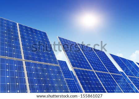 Creative solar power generation technology, alternative energy and environment protection ecology business concept: group of solar battery panels against blue sky with sun light