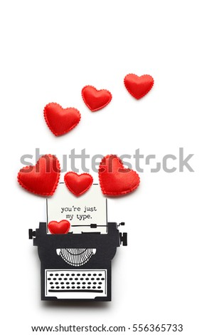 Creative valentines concept photo of a typewriter made of paper with hearts on white background.