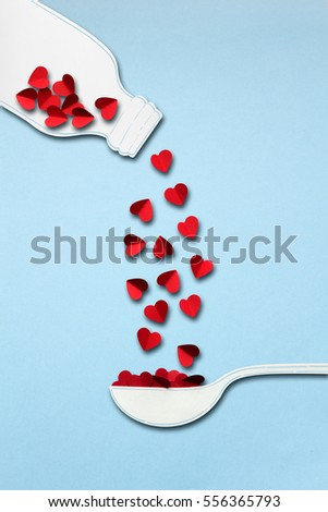 Creative valentines concept photo of bottle and spoon made of paper with hearts on blue background.