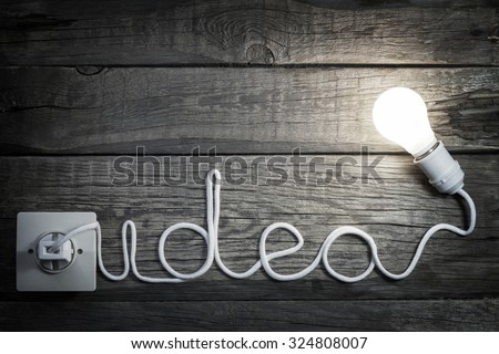 Creativity concept idea letters with bulb and wire abstract background