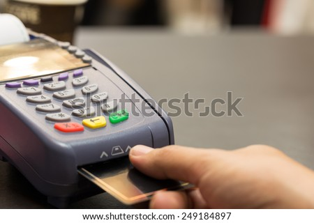Credit Card Machind with Hand Swipe Credit Card Through Terminal For Sale In Store : Selective Focus