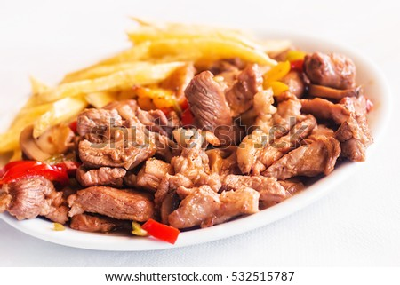 Cretan smoked pork - apaki with a side of fries (selective focus)