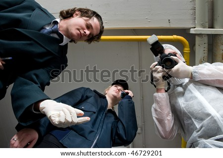 Crime scene investigations team hovering over my dead body. A police inspector, wearing rubber gloves, a policewoman using her radio, and forensic expert taking pictures as evidence