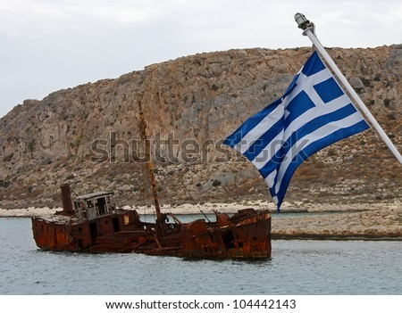 Crisis in Greece. Greek flag sailing over sank rusty ship