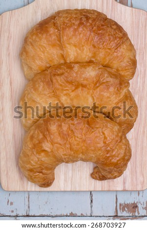 croissants on wooden-blue table background