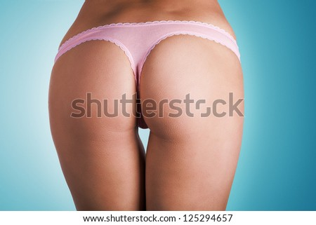Cropped image of a female model's sexy toned buttocks in pink panties