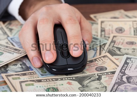Cropped image of businessman using computer mouse on banknotes