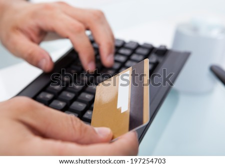 Cropped image of businessman with credit card shopping online at desk in office
