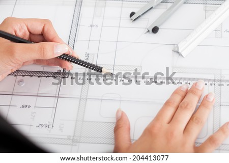 Cropped image of businesswoman working on blueprint at office