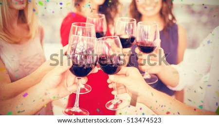 Cropped image of hand toasting wine glasses against flying colours
