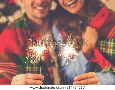 Cropped image of happy young couple holding sparklers, hugging and smiling while celebrating Christmas at home