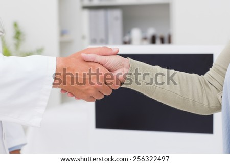 Cropped image of male doctor and female patient shaking hands in clinic