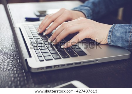 Cropped image of woman typing on laptop