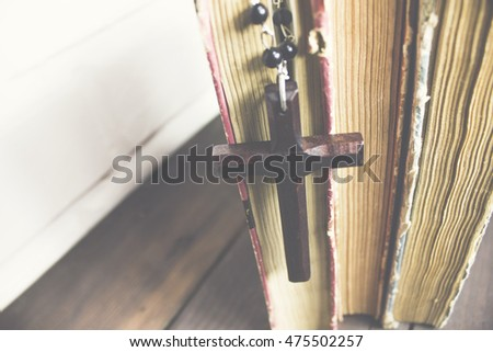 Cross with books on wooden background