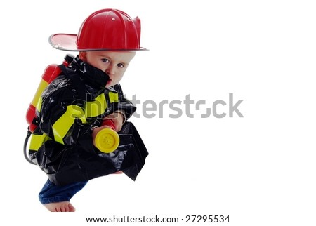 Crouching toddler fire fighter points water backpack sprayer at camera