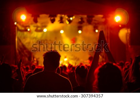 crowd at a concert in a red light, noise added