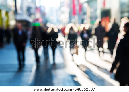 crowd of people on a shopping street in out of focus view