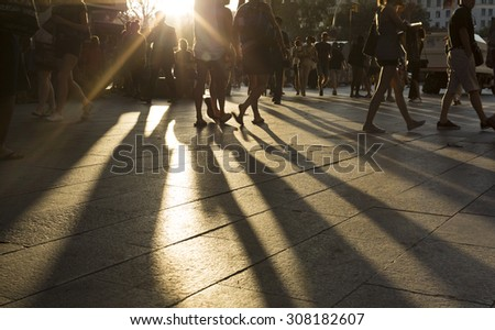 Crowds walking in a busy city district as the sun flares between them in the late afternoon creating long shadows on the ground
